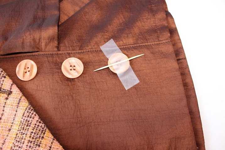 Place a straight pin or a toothpick on the button between the holes.