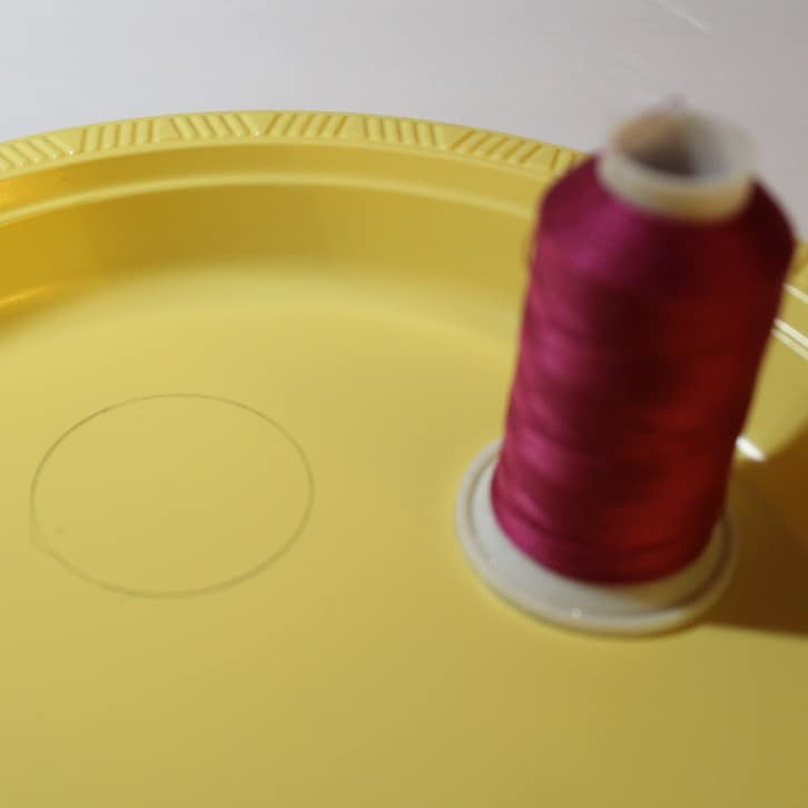 Cut a small circle from a plastic plate for the pincushion